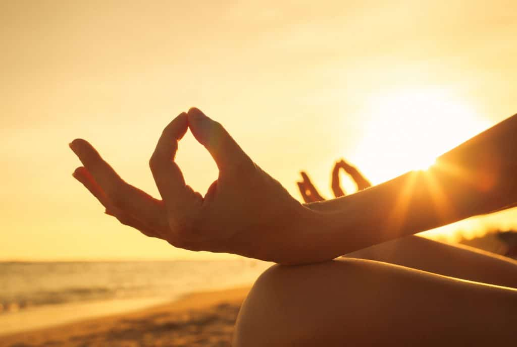woman meditating meditation beach sunset sunrise ocean